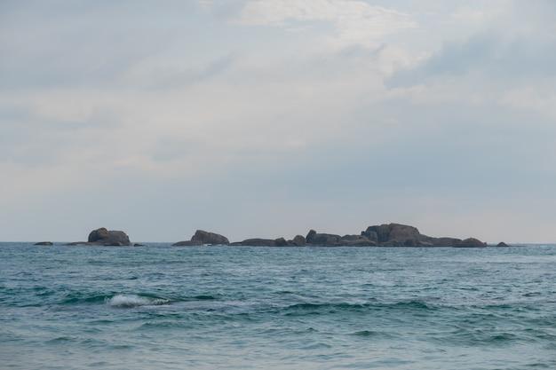 Ein steinkamm im ozean zwischen den wellen.