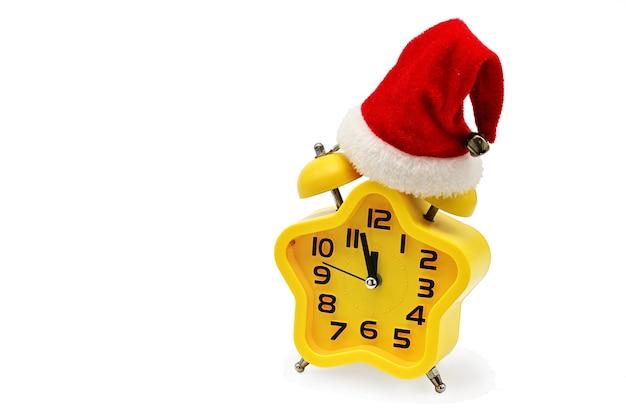 Ein sternchen weihnachtsuhr zeigt die verbleibende zeit bis mitternacht mit einer weihnachtsmannmütze auf weißem hintergrund. gelb.12, zwölf uhr