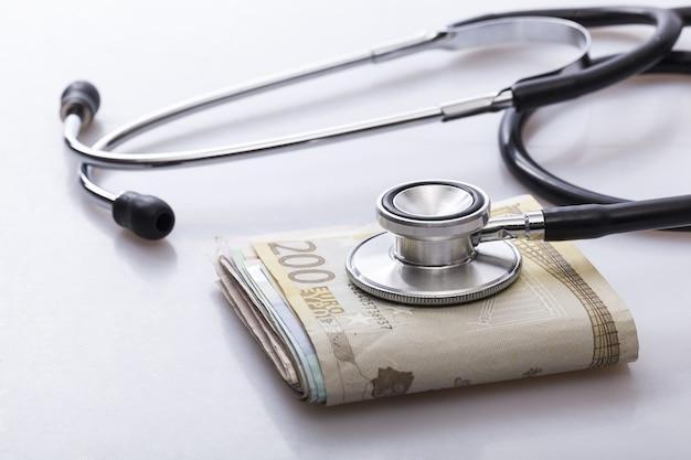 Ein stethoskop auf einem bündel euro-scheine,