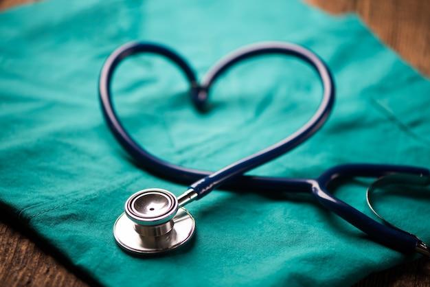 Ein stethoskop, das ein herz auf einer medizinischen uniform formt, nahaufnahme
