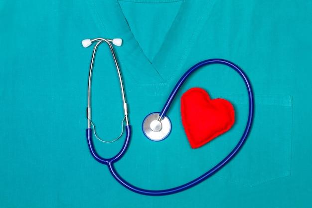 Ein stethoskop mit einem roten herz des stoffes auf einer grünen medizinischen uniform in einer draufsicht