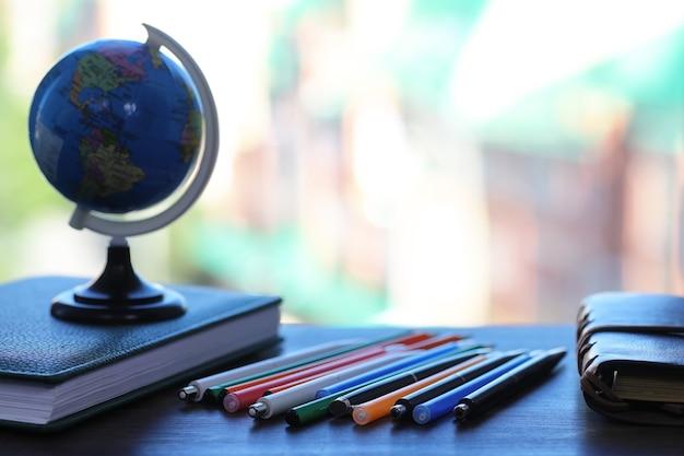 Ein stift auf dem schreibtisch und ein kleiner blauer globus