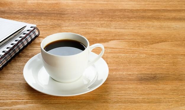 Ein stift auf einem leeren blatt briefpapier und eine tasse schwarzen kaffees auf einem holztisch.