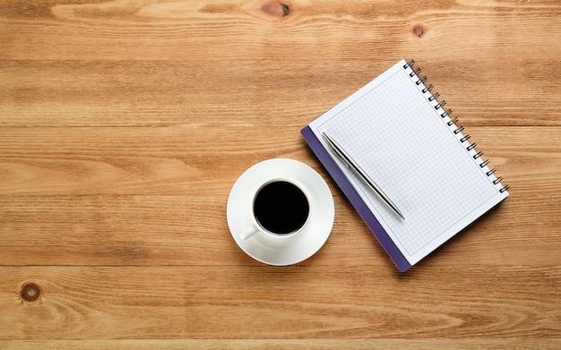 Ein stift auf einem leeren blatt notizblock und eine tasse schwarzen kaffees auf einem holztisch. gegenstände eines geschäftsmannes oder managers am arbeitsplatz.