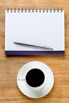 Ein stift auf leerem briefpapier und eine tasse schwarzen kaffee auf holztisch.