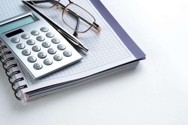 Ein stift, ein taschenrechner und eine brille liegen auf einem offenen notizblock. neben dem laptop. ein leeres blatt notizbuch mit den gegenständen eines geschäftsmannes oder buchhalters. konzept der finanzberichterstattung.