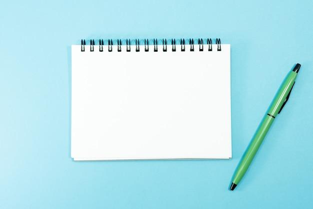 Ein stift mit einem notizbuch für das tagebuch des täglichen reisenden.