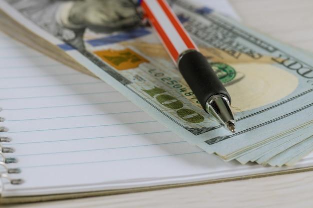 Ein stift und dollarbanknotenbargeld in einem notizbuch