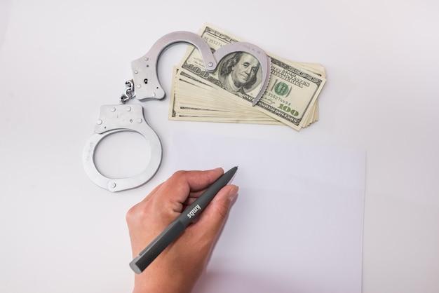 Ein stift zum schreiben von erklärungen in der hand. festnahme, kaution, verbrechen, gefängnis. handschellen und dollar.
