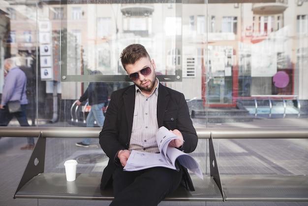 . ein stilvoller geschäftsmann in seiner brille und dokumente in seinen händen sitzt auf der bank