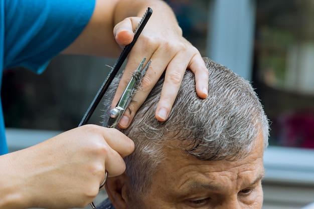 Ein stilvoller haarschnitt eines friseurs für einen mann in einem zuhause