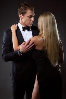 Ein stilvoller mann im anzug und ein mädchen im schwarzen abendkleid umarmen sich zärtlich und schauen sich in die augen