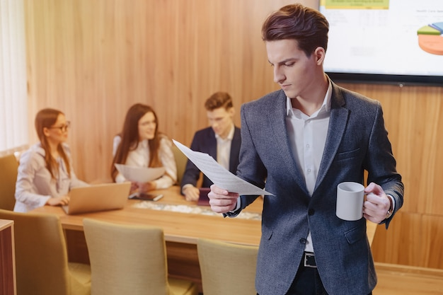 Ein stilvoller mann in einer jacke und einem hemd mit einem tasse kaffee in seiner hand steht und liest dokumente auf dem hintergrund von arbeitskollegen im büro