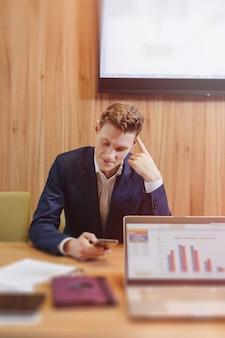 Ein stilvoller mann in jacke und hemd sitzt mit seinen kollegen am schreibtisch und arbeitet im büro mit dokumenten