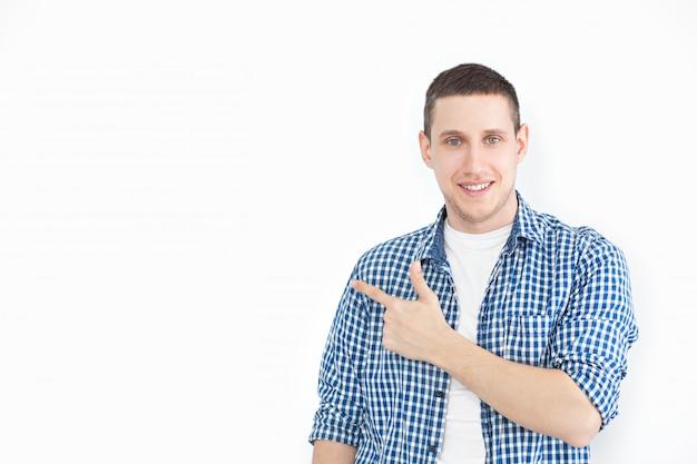 Ein stilvoller unrasierter mann in einem hemd zeigt auf eine kopie des raumes an einer weißen wand, wie etwas schönes zeigt, lächelnd aussieht und für ein produkt wirbt. schau hier! menschen, werbung, emotion konzept