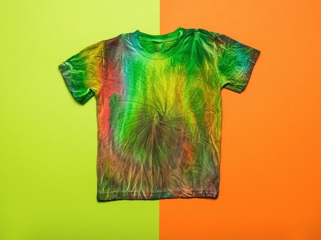 Ein stilvolles handbemaltes batik-t-shirt auf orange-grünem hintergrund. flach liegen.