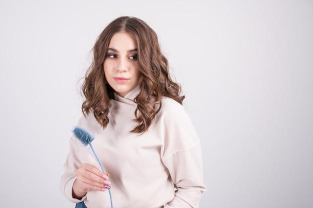 Ein stilvolles junges mädchen in einer beigen kleidung, die getrocknete blumen in ihren händen weißem studiohintergrund hält