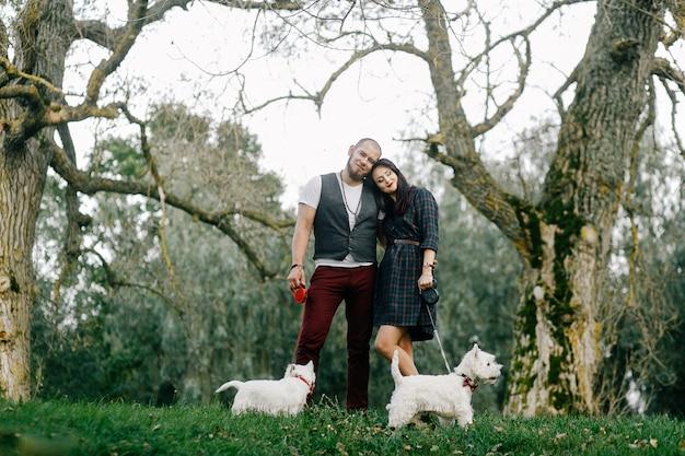 Ein stilvolles paar schlendert mit zwei weißen hunden durch den park