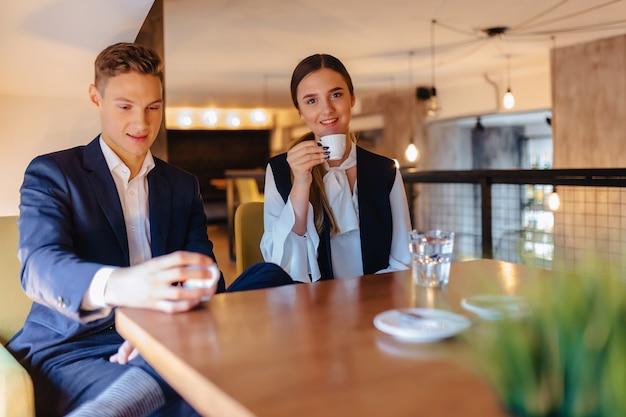 Ein stilvolles paar trinkt morgenkaffee im café, junge geschäftsleute und freiberufler