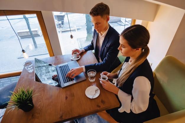Ein stilvolles paar trinkt morgenkaffee im café und arbeitet mit einem laptop