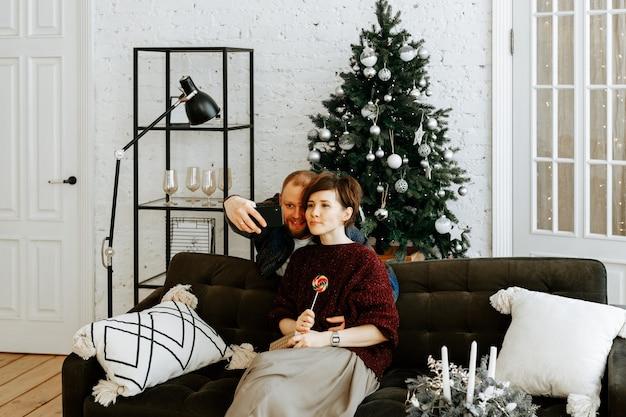 Ein stilvolles verliebtes paar macht ein selfie auf seinem smartphone vor dem hintergrund eines weihnachtsbaumes zu hause