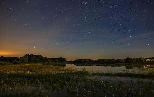 Ein strahlender sonnenuntergang am nachthimmel. die landschaft mit fluss und bäumen wird auf einer langen belichtungszeit fotografiert.