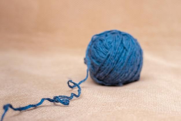 Ein strang aus blauem garn zum stricken auf einem orangefarbenen stoff