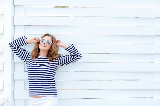 Ein straßenfoto einer jungen brünetten frau in einem leeren weißen hintergrund schaut beiseite, während sie neben dem hellblauen holzzaun steht. horizontales modell. leerer platz für text oder design.