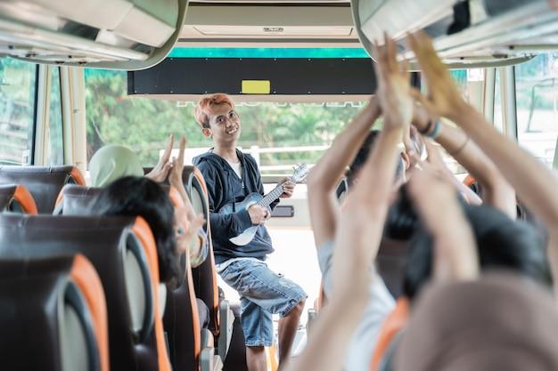 Ein straßenmusiker, der ein ukulelen-musikinstrument benutzt, und busfahrgäste singen und klatschen auf reisen in die hände