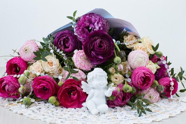 Ein strauß aus ranunkeln, rosen, transparenten perlen und einem weißen engel