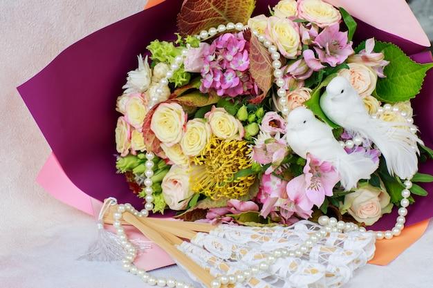Ein strauß aus rosen, hortensien und zwei weißen tauben, perlenperlen