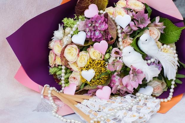Ein strauß aus rosen, hortensien und zwei weißen tauben, satinherzen, perlen