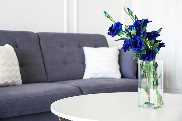 Ein strauß blauer blumen in einer glasvase auf einem runden tisch neben einem blauen sofa.