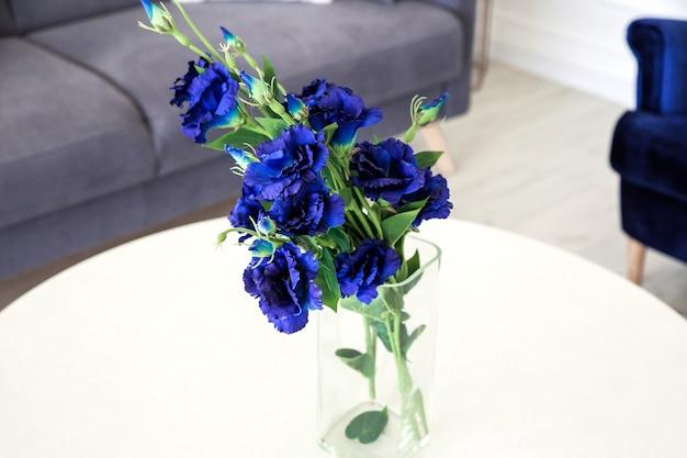 Ein strauß blauer blumen in einer glasvase auf einem runden tisch neben einem grauen sofa.