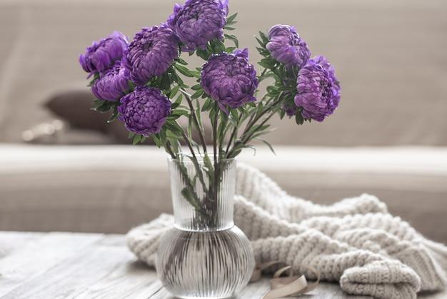 Ein strauß blauer chrysanthemen in einer glasvase auf dem tisch im inneren des raumes.