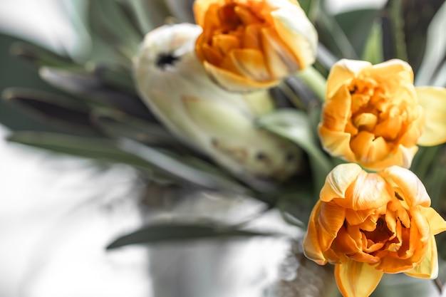 Ein strauß exotischer blumen aus königlichem protea und leuchtenden tulpen. tropische pflanzen in floristischer zusammensetzung.
