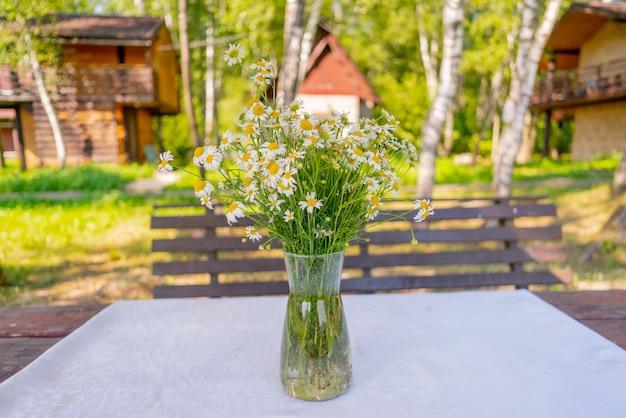 Ein strauß feldmargeriten auf dem tisch in einer vase.