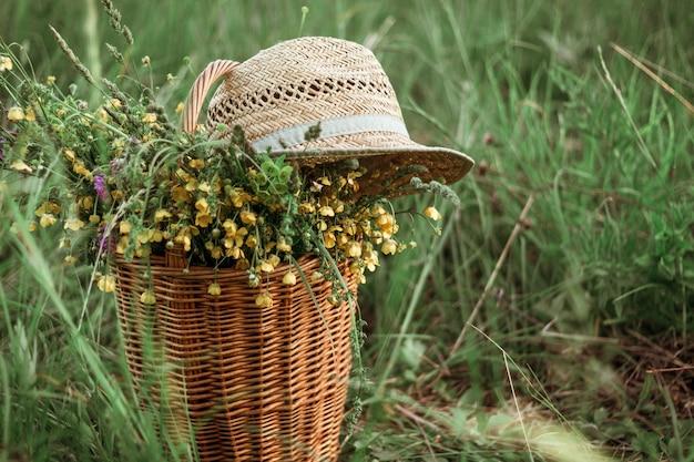 Ein strauß gelb-blauer wildblumen in einem weidenkorb und ein sommerstrohhut auf dem feld. platz kopieren. selektiver fokus