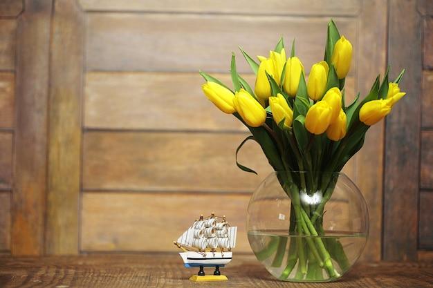 Ein strauß gelber tulpen in einer vase auf dem boden. ein geschenk zum tag einer frau aus gelben tulpenblumen. schöne gelbe blumen in einer vase an der wand.