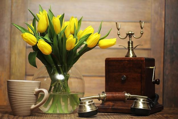 Ein strauß gelber tulpen in einer vase auf dem boden. ein geschenk zum tag einer frau aus gelben tulpenblumen. schöne gelbe blumen in einer vase an der wand. Premium Fotos