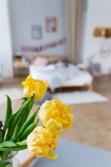 Ein strauß gelber tulpen in nahaufnahme in einem hellen, gemütlichen schlafzimmer