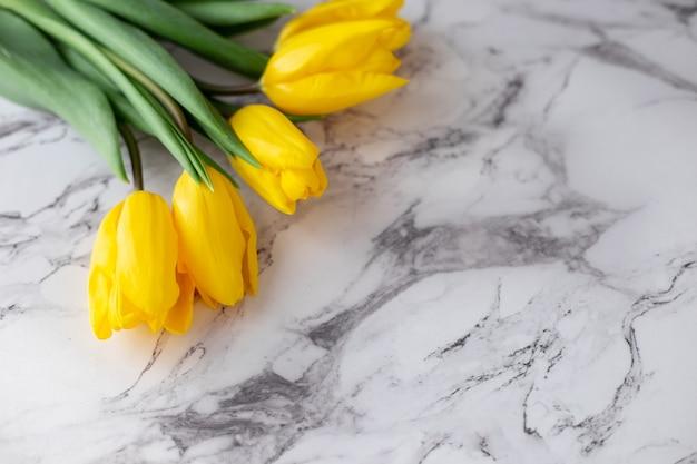 Ein strauß gelber tulpen liegt in der oberen linken ecke auf einem granit