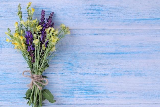 Ein strauß gelber und lila wildblumen auf einem blauen holztisch.