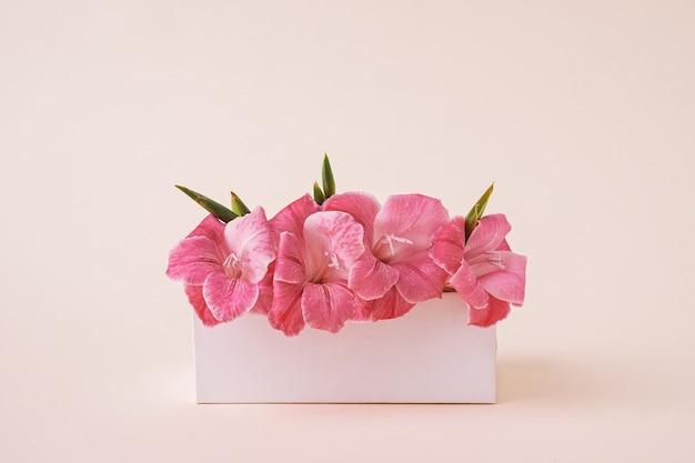 Ein strauß gladiolen zu einer geschenkbox für eine hochzeit und einen urlaub im retro-stil.