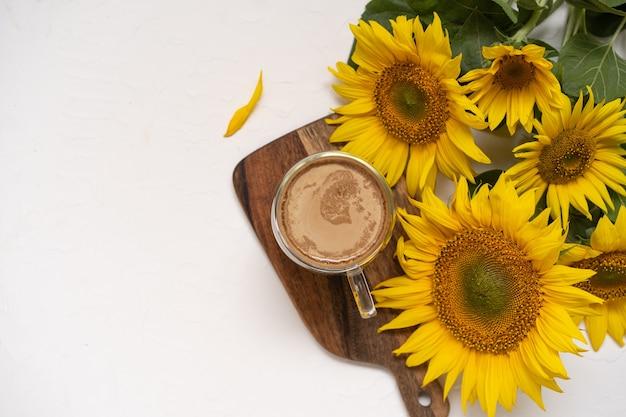 Ein strauß großer sonnenblumen und heißer kaffee.