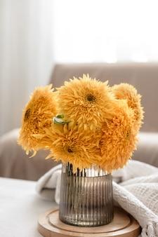 Ein strauß heller sonnenblumen in einer glasvase auf unscharfem hintergrund im inneren des raumes.