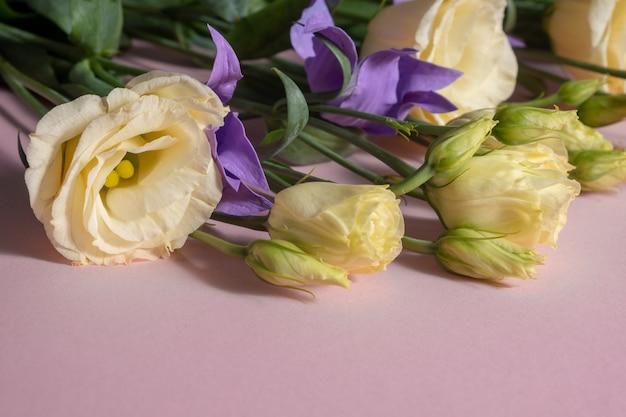 Ein strauß hellgelber eustoma und lila clematis auf einer rosa oberfläche.