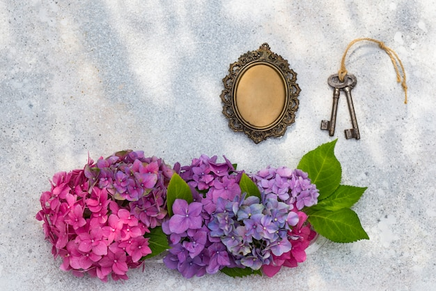 Ein strauß hortensien, ein alter rahmen für fotos und schlüssel