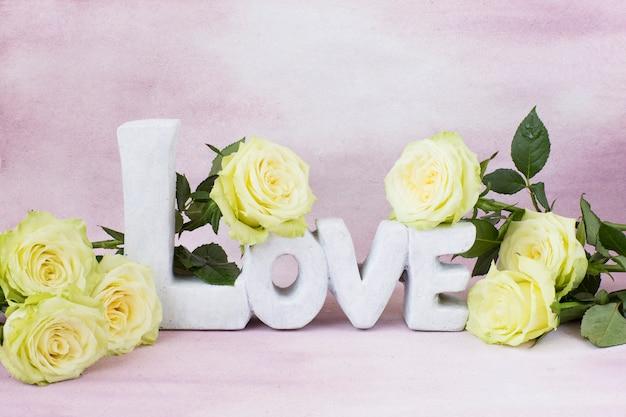 Ein strauß leichter rosen und das wort liebe aus stein. freier platz für text