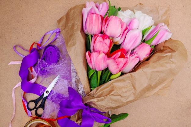 Ein strauß leuchtend zarter rosa tulpen mit grünem laub in bastelpapier mit bunten bändern und scheren. die arbeit des floristen.